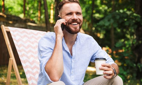 Photo of happy young bearded man outdoors talking by mobile phone drinking coffee.